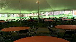 bright orange tables setup under a tent